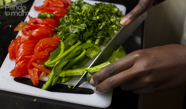 while the chicken is cooking you can prepare the other ingredients: slice 2 tomatoes, slice half a green pepper, chop up about a cup of dhania an slice a mid-sized onion