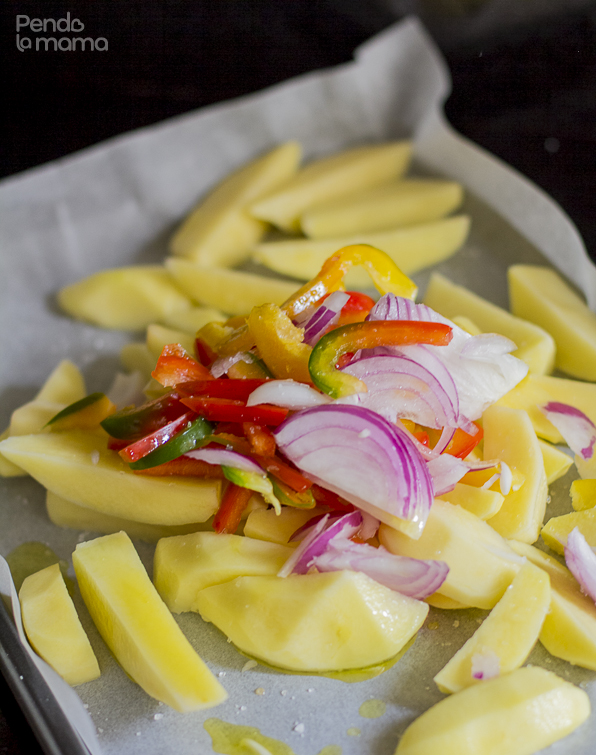 potato wedges, onion slices, red and yellow pepper slices, in an oven pan covered with parchment paper, sprinkled with oil and salt